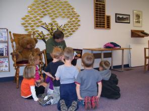 Librarian Ron reads for story time in front of the Memorial tree.