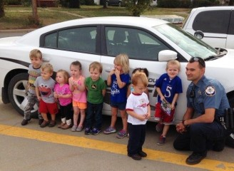 Children explore a police car.
